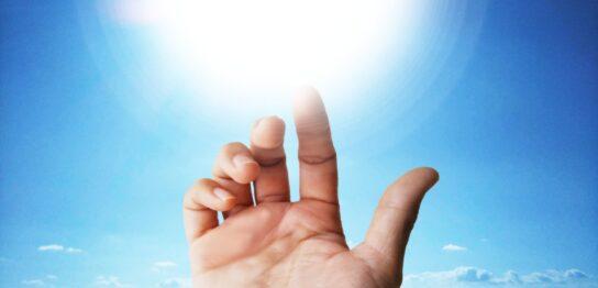 空にある光に差し伸べる手